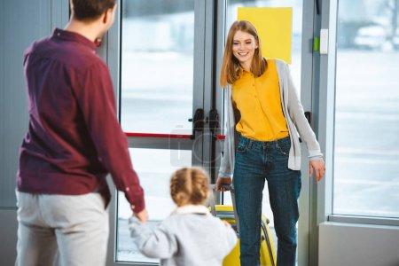 Photo pour Mise au point sélective de jolie femme regardant de mari et sa fille à l'aéroport - image libre de droit