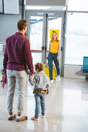 back view of man holding hands with daughter and looking at wife with luggage