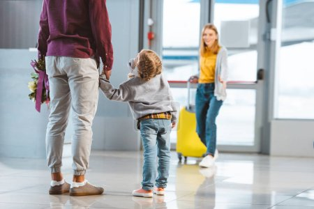 selective focus of child holding hands with father near mother with baggage on background