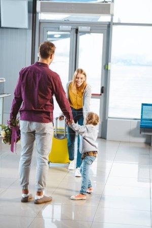 Photo pour Mère avec des bagages regardant mari et fille se tenant la main lors d'une réunion à l'aéroport - image libre de droit