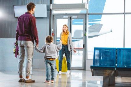 Photo pour Foyer sélectif de la mère avec des bagages regardant mari et fille se tenant la main lors d'une réunion à l'aéroport - image libre de droit