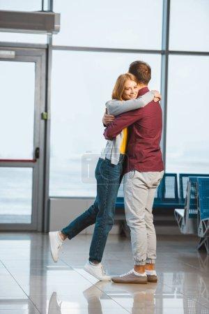 Photo pour Attrayant femme câlin copain dans salle d'attente - image libre de droit