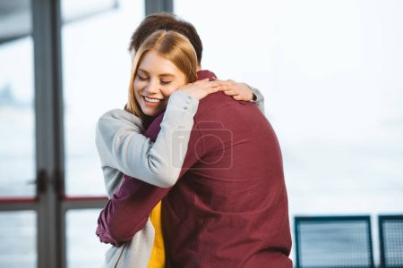 attractive woman smiling with closed eyes while hugging boyfriend