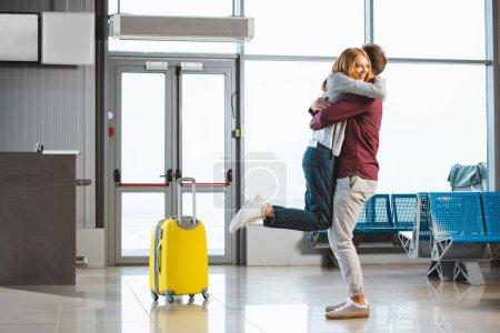 Photo pour Attrayant femme câlin copain dans salle d'attente près de valise - image libre de droit