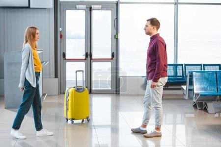 Photo pour Bel homme regardant petite amie dans le hall d'attente de l'aéroport - image libre de droit