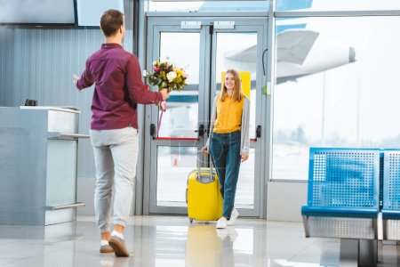 back view of boyfriend with flowers meeting happy girlfriend with suitcase in airport