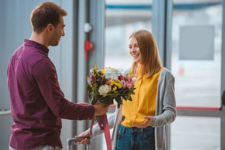 Photo pour Beau petit ami tenant des fleurs tout en rencontrant petite amie heureuse à l'aéroport - image libre de droit