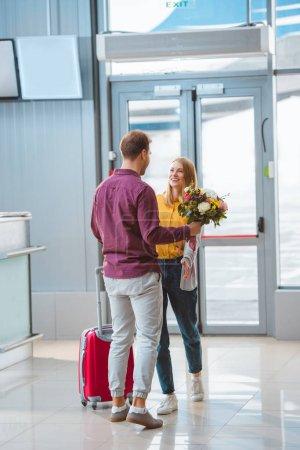 Photo pour Petit ami tenant des fleurs et rencontrant petite amie heureuse avec valise à l'aéroport - image libre de droit