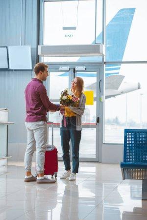 Photo pour Petit ami joyeux donnant des fleurs à petite amie à l'aéroport - image libre de droit