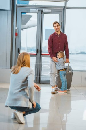 selective focus of cute child hugging father with suitcase in airport