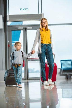 Photo pour Belle mère tenant la main avec fille mignonne tout en marchant avec des valises à l'aéroport - image libre de droit