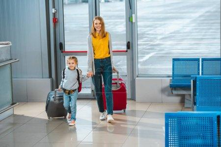 Photo pour Joyeuse mère tenant la main avec fille mignonne tout en marchant avec des valises à l'aéroport - image libre de droit