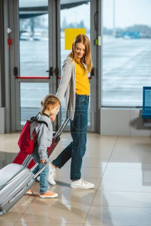 Photo for Attractive mother looking at daughter and walking with baggage in airport - Royalty Free Image