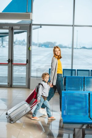 attractive mother holding hands with daughter and walking with baggage in airport