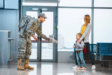 Photo for Dad in military uniform giving teddy bear to daughter standing near mother in airport - Royalty Free Image