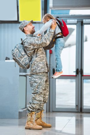 Photo for Happy father in military uniform holding in arms cute daughter in airport - Royalty Free Image