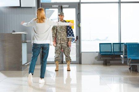 Photo pour Bonne copine à bras ouverts copain vêtus d'uniformes militaires avec le drapeau américain à l'aéroport de la réunion - image libre de droit