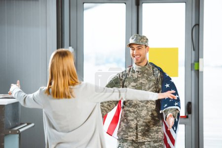 selective focus of happy boyfriend in military uniform looking at girlfriend with opened arms  in airport