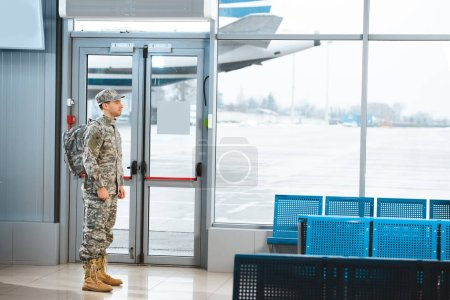 Photo pour Vétéran en uniforme militaire debout avec sac à dos dans le salon de départ - image libre de droit