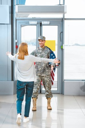 back view of woman meeting boyfriend in military uniform with american flag in airport