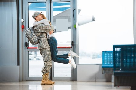 Photo for Happy boyfriend in military uniform holding in arms girlfriend in airport - Royalty Free Image