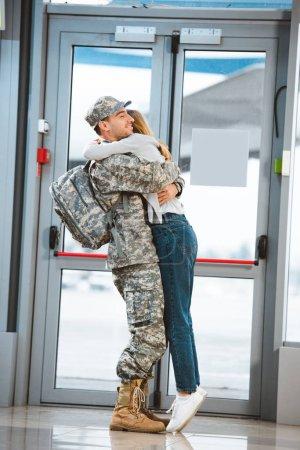 Photo pour Petite amie heureuse étreignant petit ami joyeux en uniforme militaire à l'aéroport - image libre de droit