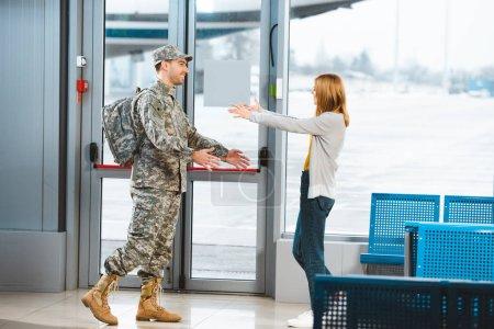Photo pour Vétéran heureux en uniforme militaire regardant petite amie et debout avec les bras ouverts à l'aéroport - image libre de droit