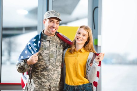 smiling man in military uniform standing with girlfriend and holding american flag in airport
