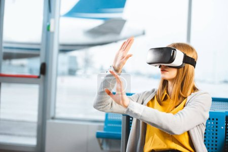 Photo for Woman wearing virtual reality headset while sitting in airport - Royalty Free Image