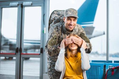 Photo pour Beau vétéran fermer les yeux de joyeuse petite amie à l'aéroport - image libre de droit