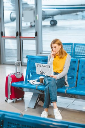 Photo for Attractive woman reading travel newspaper near suitcase in airport - Royalty Free Image