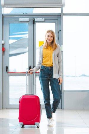 Photo pour Jolie femme debout avec la valise dans la salle d'attente - image libre de droit
