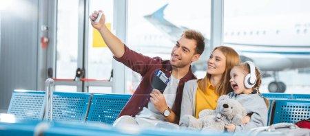 Photo pour Joyeux père prenant selfie et souriant avec femme et fille montrant la langue dans l'aéroport - image libre de droit