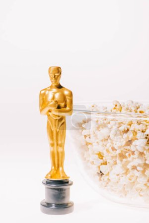Photo for Shiny oscar award with popcorn bowl isolated on white - Royalty Free Image