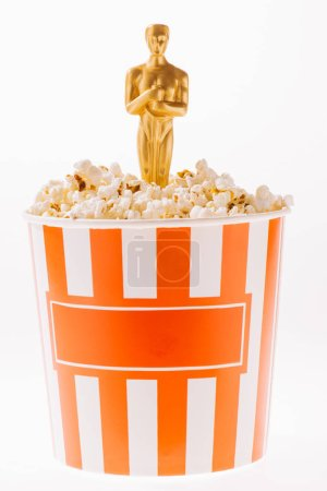 Photo for Shiny oscar award in popcorn cup isolated on white - Royalty Free Image