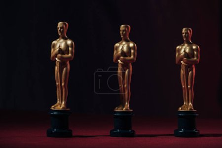 Photo for Row of golden oscar awards on black background - Royalty Free Image