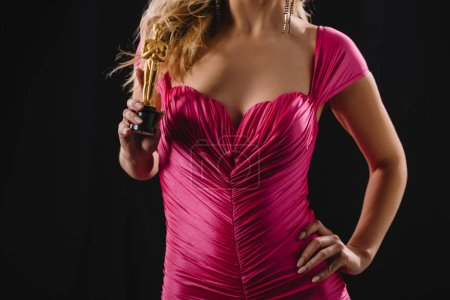 Photo for Cropped view of woman in pink holding oscar award isolated on black - Royalty Free Image