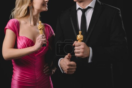 Photo for Partial view of man showing thumb up sign and holding oscar awards with woman isolated on black - Royalty Free Image