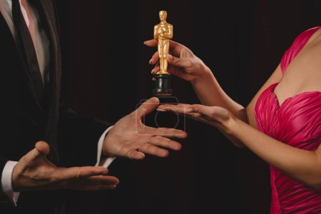 Photo for Cropped view of woman presenting oscar award to man with outstretched hands isolated on black - Royalty Free Image