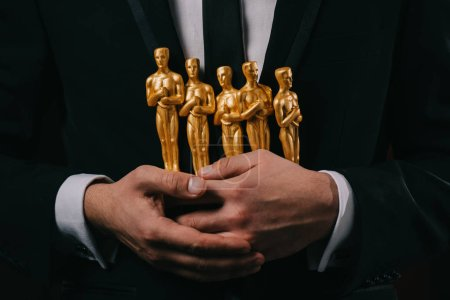 Photo for Partial view of man in suit holding oscar awards isolated on black - Royalty Free Image