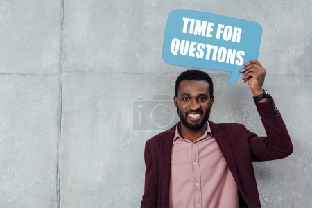 "Photo for Smiling african american casual businessman looking at camera and holding speech bubble with ""time for questions"" lettering on grey background - Royalty Free Image"