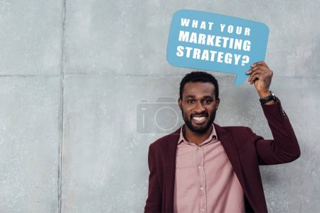 "Photo for Smiling african american casual businessman looking at camera and holding speech bubble with ""what your marketing strategy?"" lettering on grey background - Royalty Free Image"