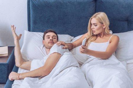 Schockierte junge Frau zeigt verwirrtem Freund Smartphone im Bett, misstraut Konzept