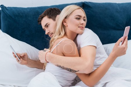 Photo for Young couple hugging and using smartphones in bed, relationship problem concept - Royalty Free Image