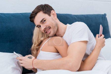 junges Paar umarmt und benutzt Smartphones im Bett, Mann lächelt in die Kamera