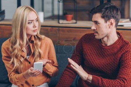 young couple quarreling about smartphone and looking at each other, relationship problem concept