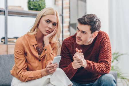 Ehemann schaut unglückliche junge Frau mit Smartphone an und schaut zu Hause in die Kamera, Beziehungsprobleme