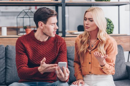 Photo for Emotional young couple quarreling about smartphone at home, jealousy concept - Royalty Free Image