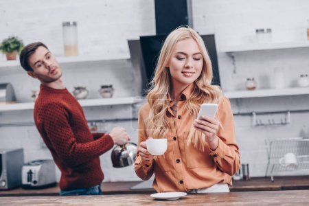 Photo for Jealous young man looking at smiling girlfriend holding cup and using smartphone in kitchen - Royalty Free Image