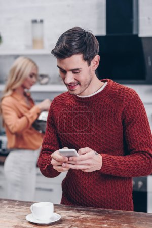 Photo for Smiling young man texting via smartphone while girlfriend holding kettle behind in kitchen - Royalty Free Image